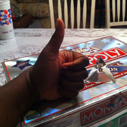 Marcus giving a thumbs up in front of a Monopoly game